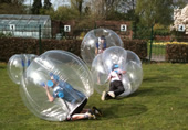 Four youngsters rolling around in BodyZorbs
